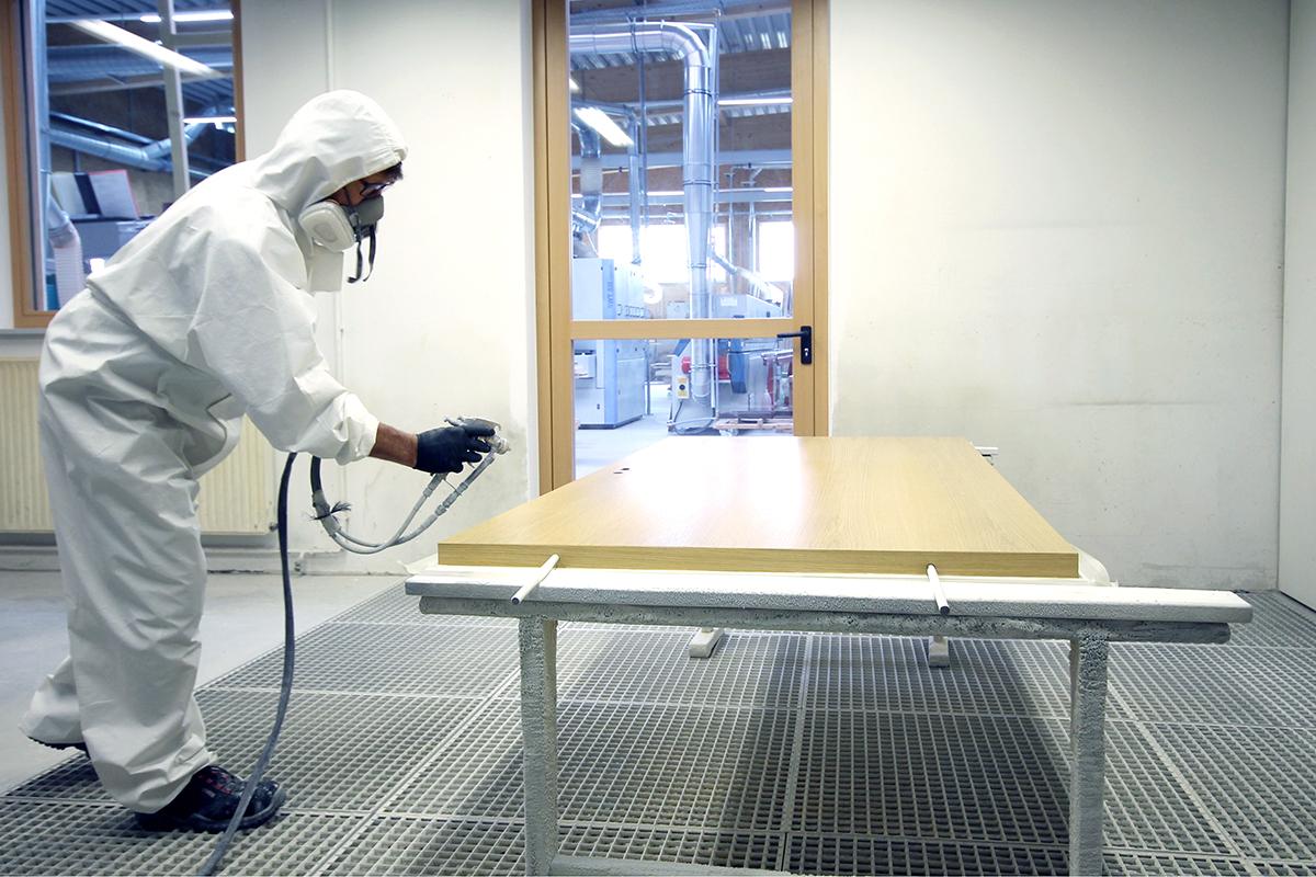 Mann in weißem Schutzanzug lackiert Tür